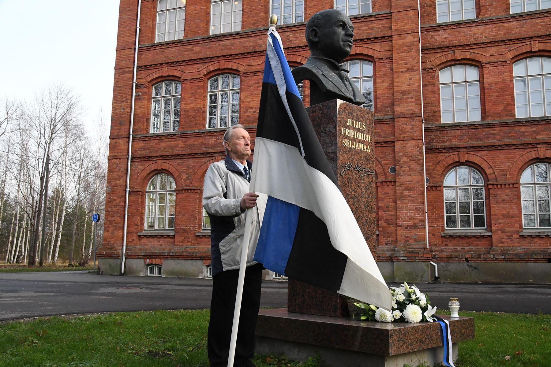 Julius Friedrich Seljamaa ausamba juures seisab ajaloolise lipuga auvalves Jaan Roosnurm, Eesti lipu seltsi liige. Foto Urmas Saard