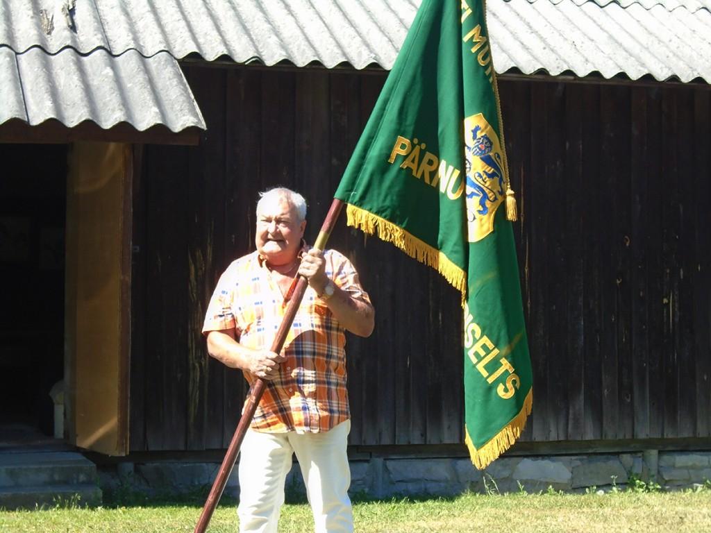 Mati Rosenstein Pärnu-Jaagupi muinsuskaitse seltsi lipuga muuseumi õuel
