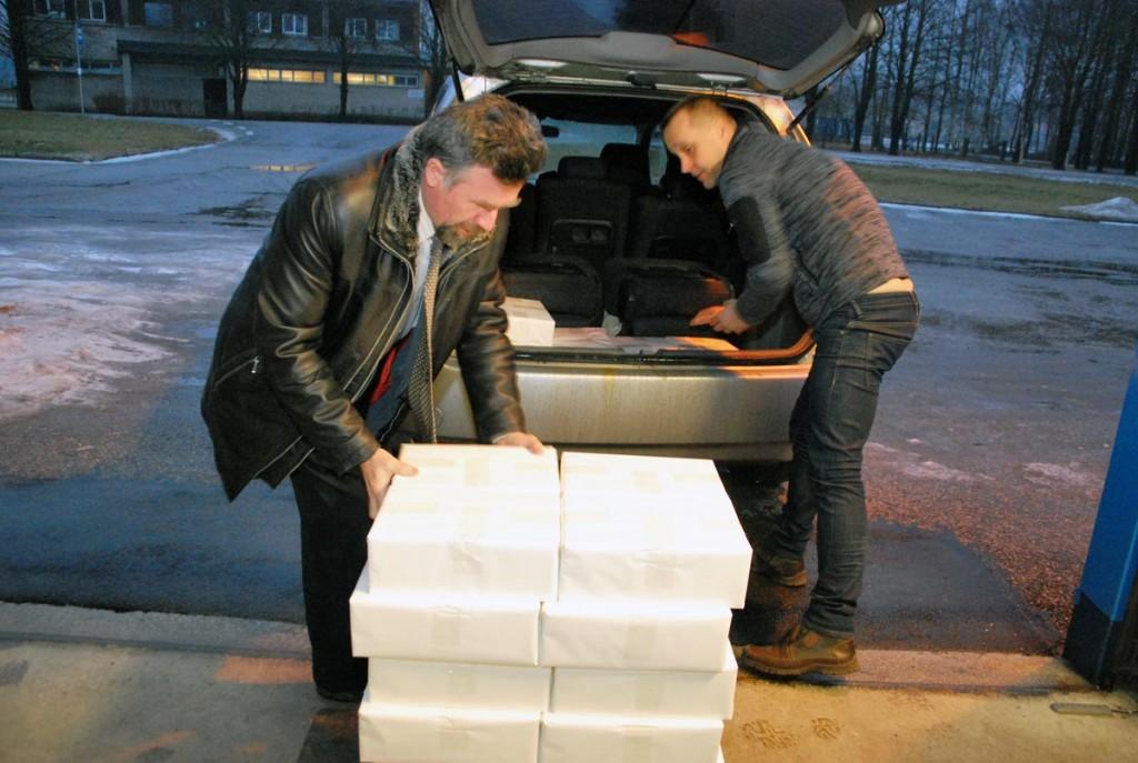 Mati Sutt tõstab koos Hansprindi töötajaga raamatute pakid autole Foto Urmas Saard