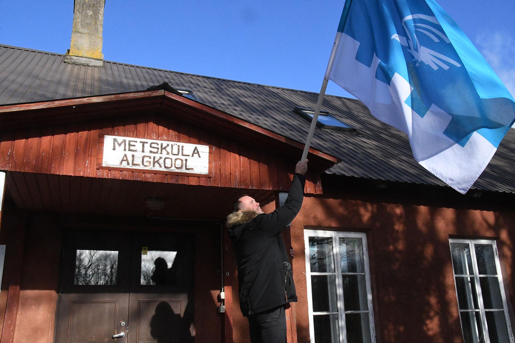 Metsküla kooli vilistlane Märten Hermik vabastab tuulest keerdu kammitsetud oma kooli lipu uuesti vabalt lehvima. Foto Urmas Saard